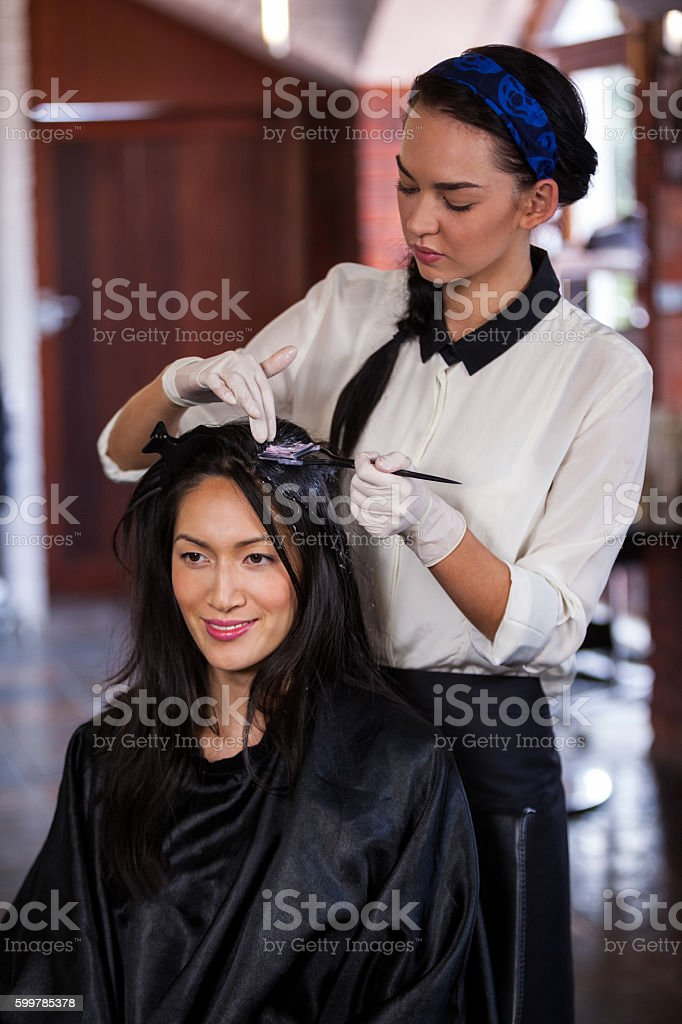 Hairdresser dyeing hair of her client stock photo