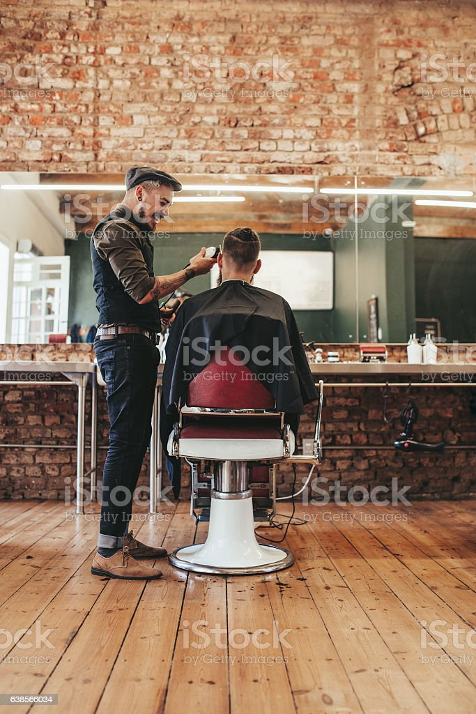 Hairdresser giving haircut to client at salon stock photo