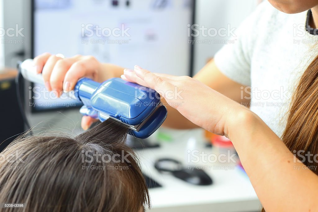 Hairdresser hairstyle models using the straightener . stock photo