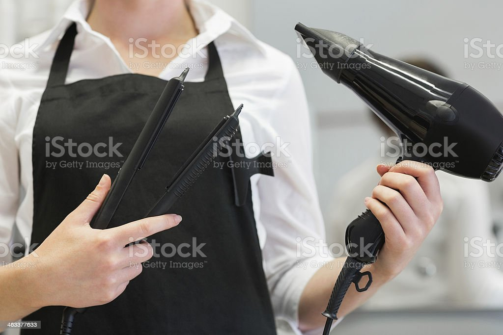 Hairdresser holding hair dryer and straightener royalty-free stock photo