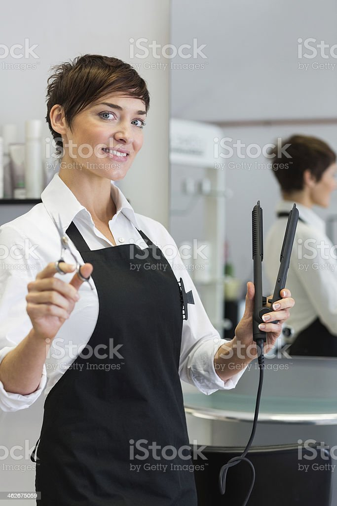 Hairdresser holding scissors and hair straightener royalty-free stock photo