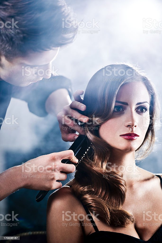 Hairdresser making glamorous retro hairstyle. stock photo