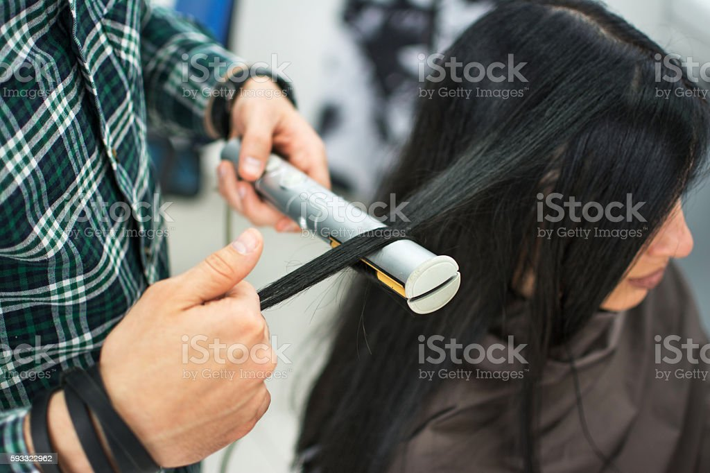 Hairdresser straightening long black hair with hair irons. stock photo