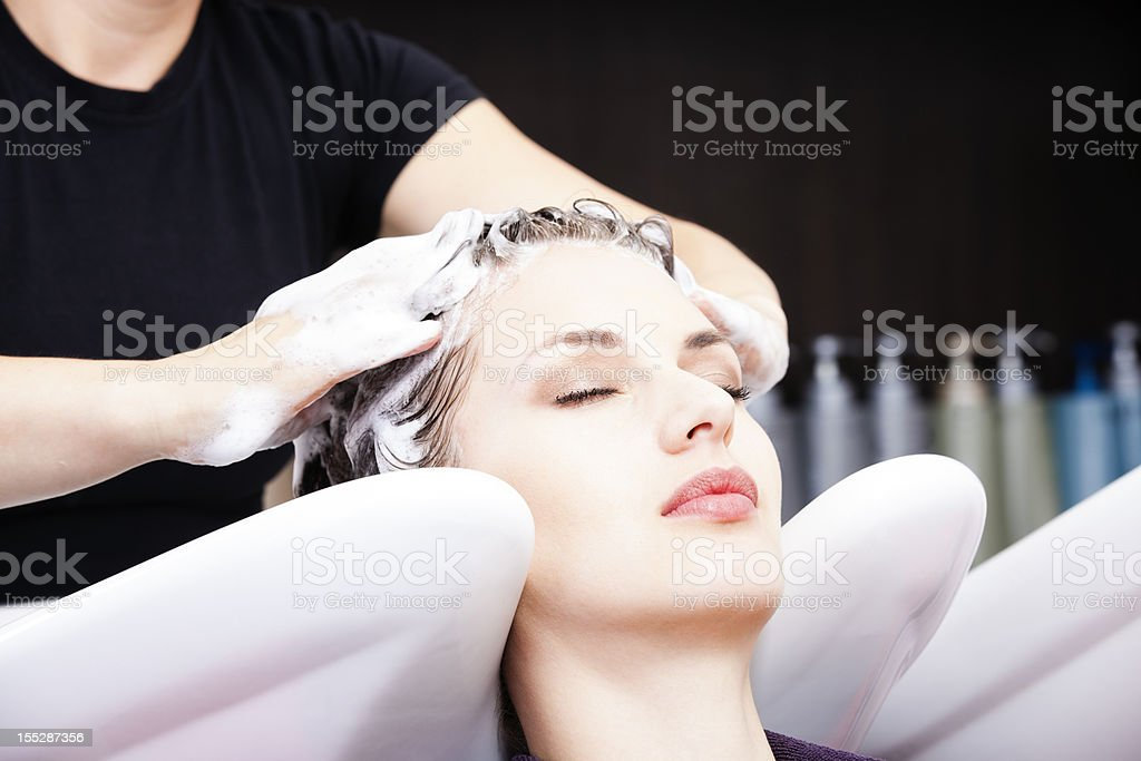 Hairdresser washing woman's hair after coloring stock photo