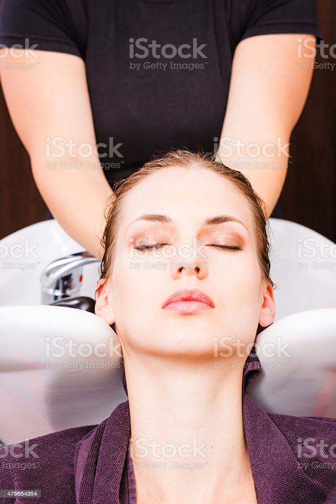 Hairdresser washing woman's hair stock photo