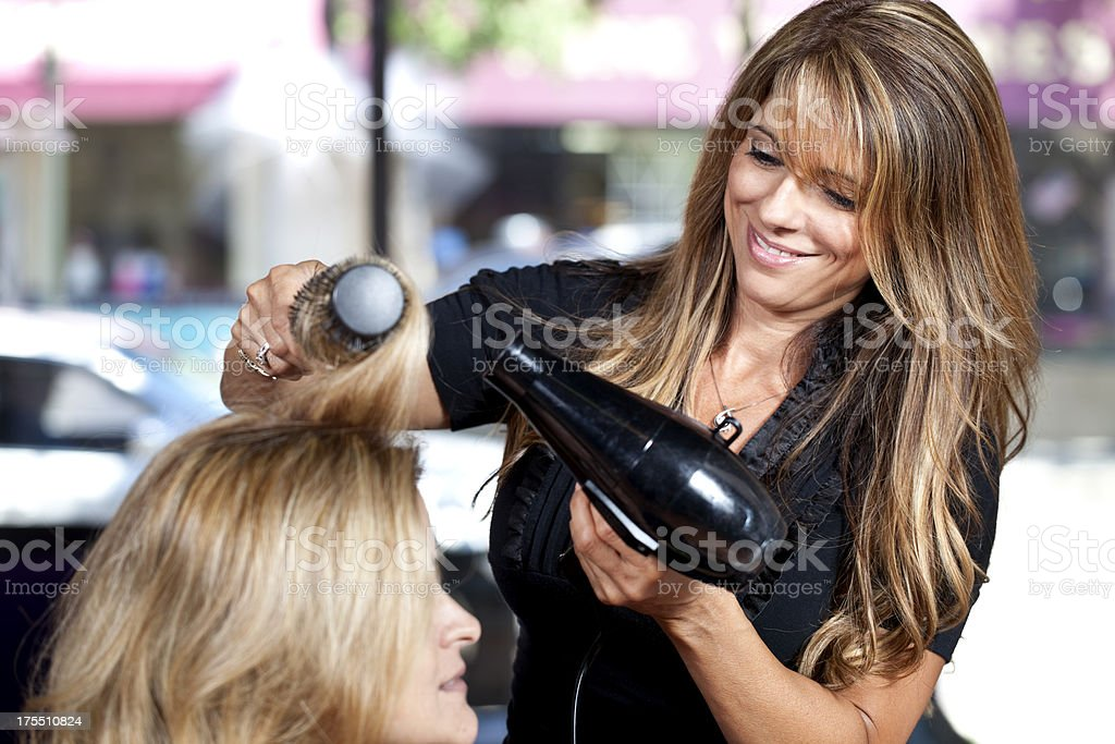Hairdresser working  blowing out hair in salon, smiling stock photo