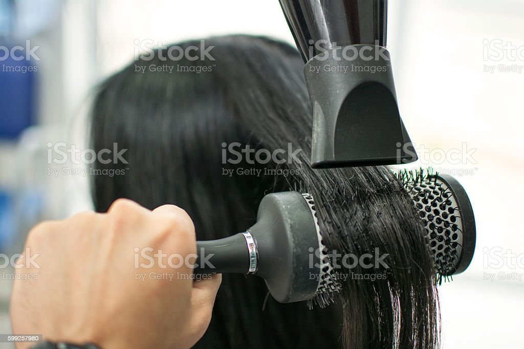 Hairdressers drying long hair with blow dryer and round brush. stock photo