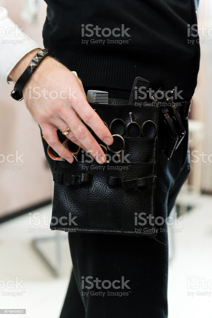 hairdresser's hand choosing from a variety of professional cutting instrument stock photo