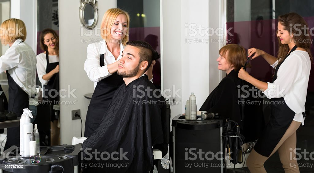 Hairdressers with scissors cutting hair stock photo