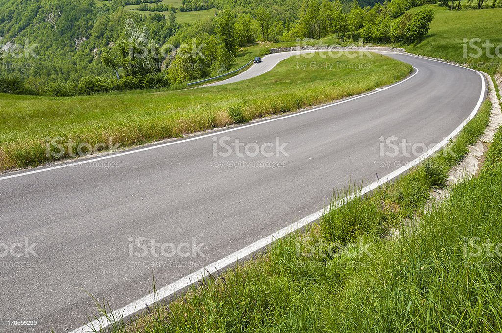 Hairpin bend in a winding road thru green countryside royalty-free stock photo