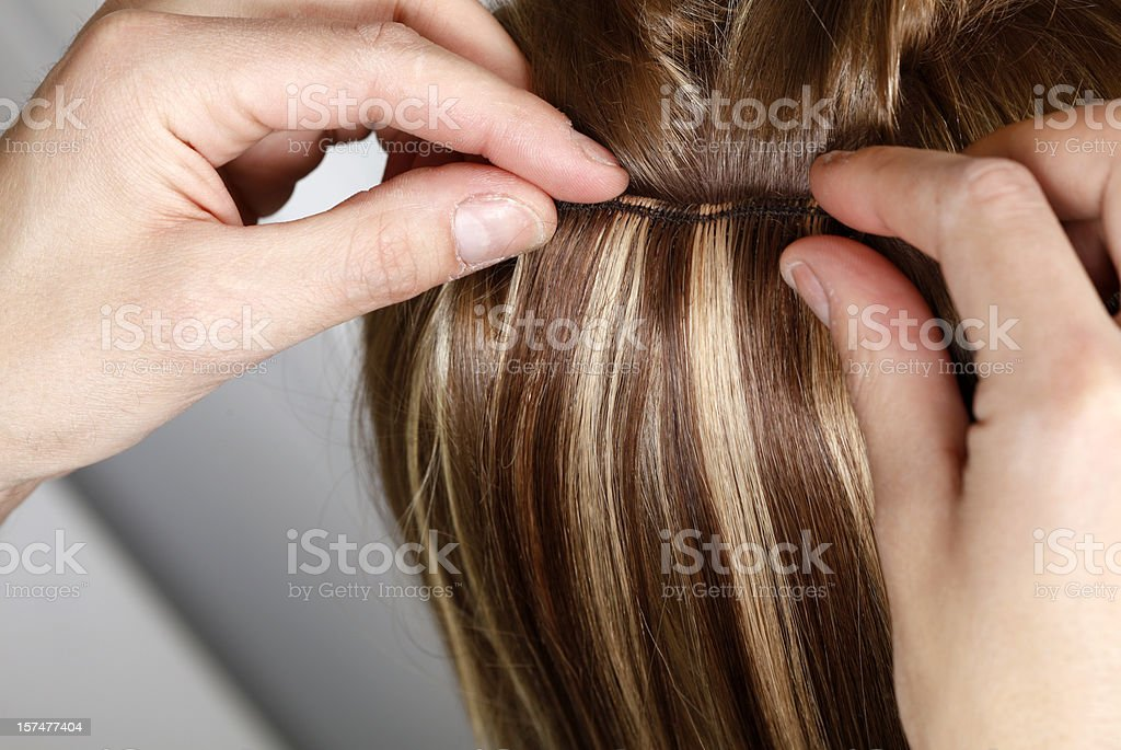 Hairstylist Applying Hair Extensions stock photo