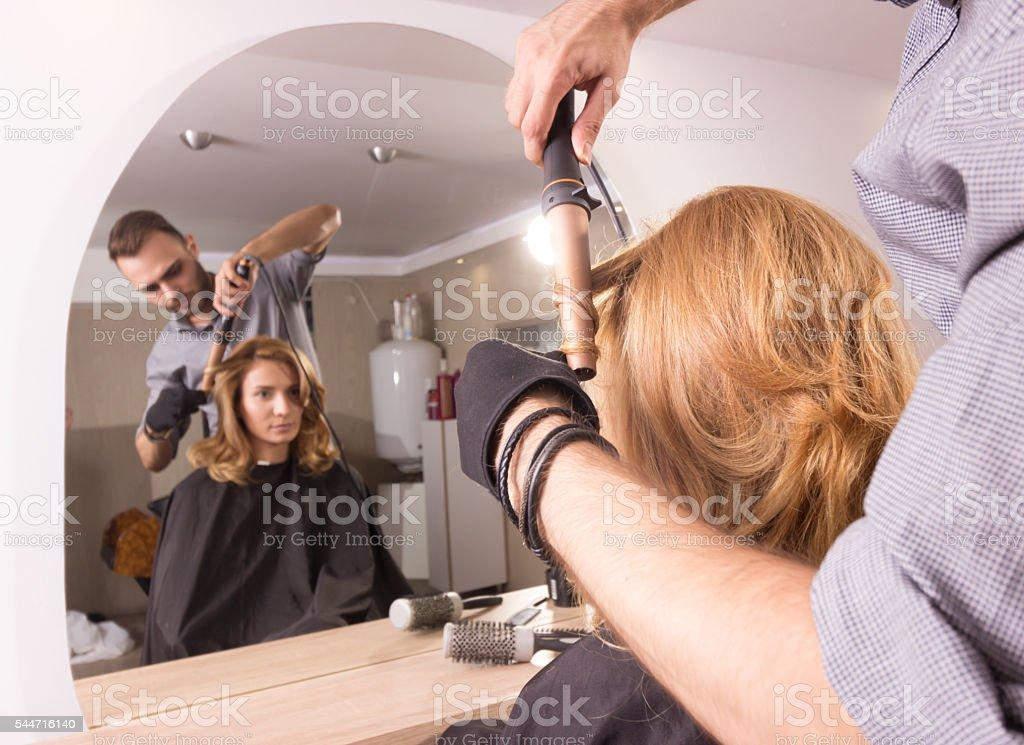 Hairstylist curling hair iron closeup stock photo