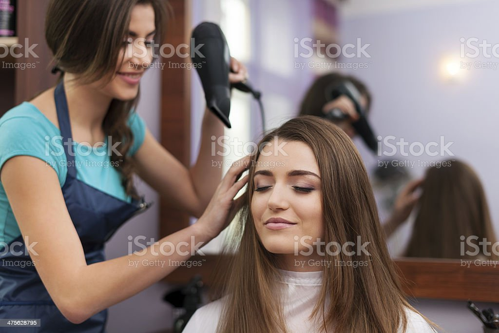 Hairstylist drying woman's hair royalty-free stock photo