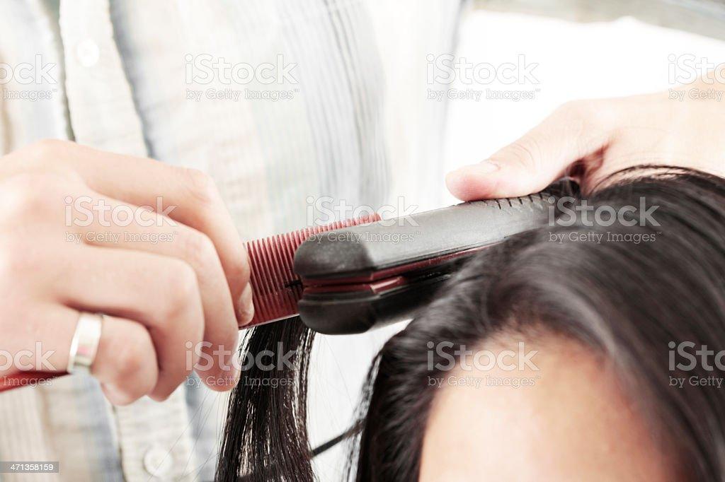 Hairstylist Flat Ironing Hair stock photo