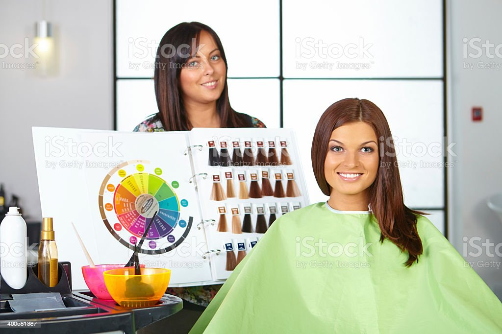 Hairstylist holding a board with dye color options in salon stock photo