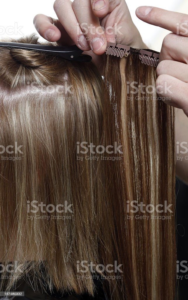 Hairstylist Putting in Hair Extensions stock photo