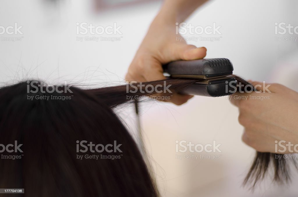 Hairstylist straightening some hair royalty-free stock photo