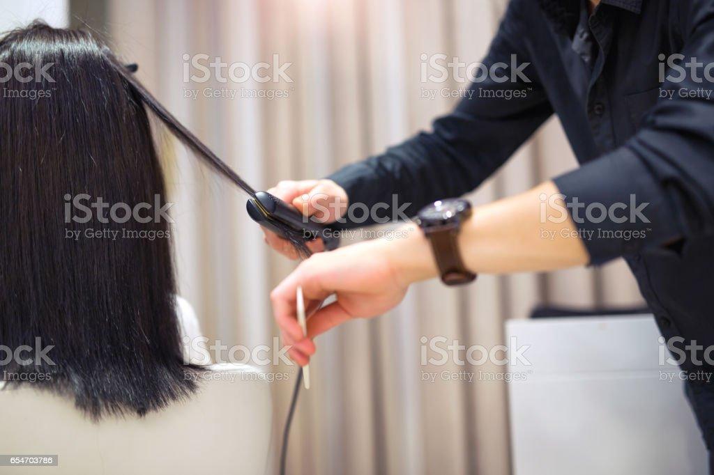 Hairstylist straightening some hair stock photo
