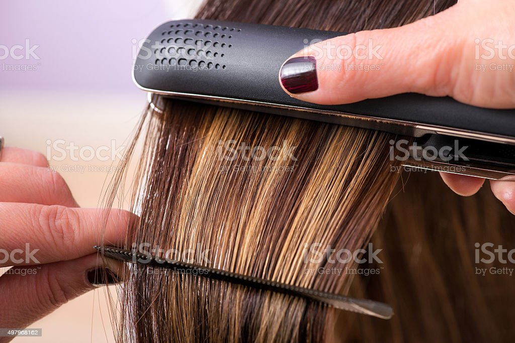 Hairstylist straightening the hair of a client stock photo