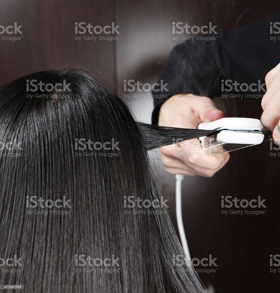 Hairstylist Straitening a Section of Hair stock photo