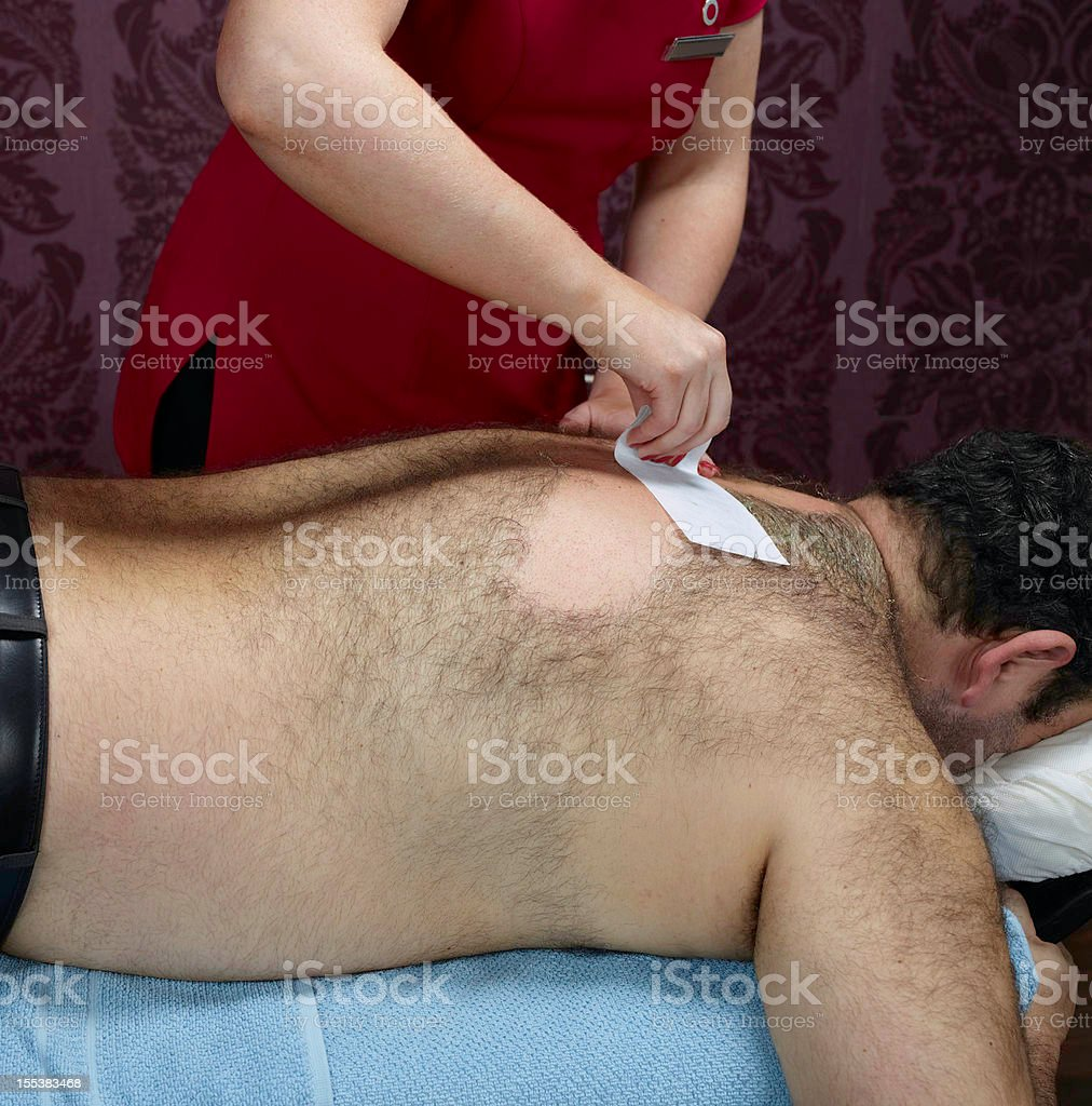Hairy male back waxing stock photo