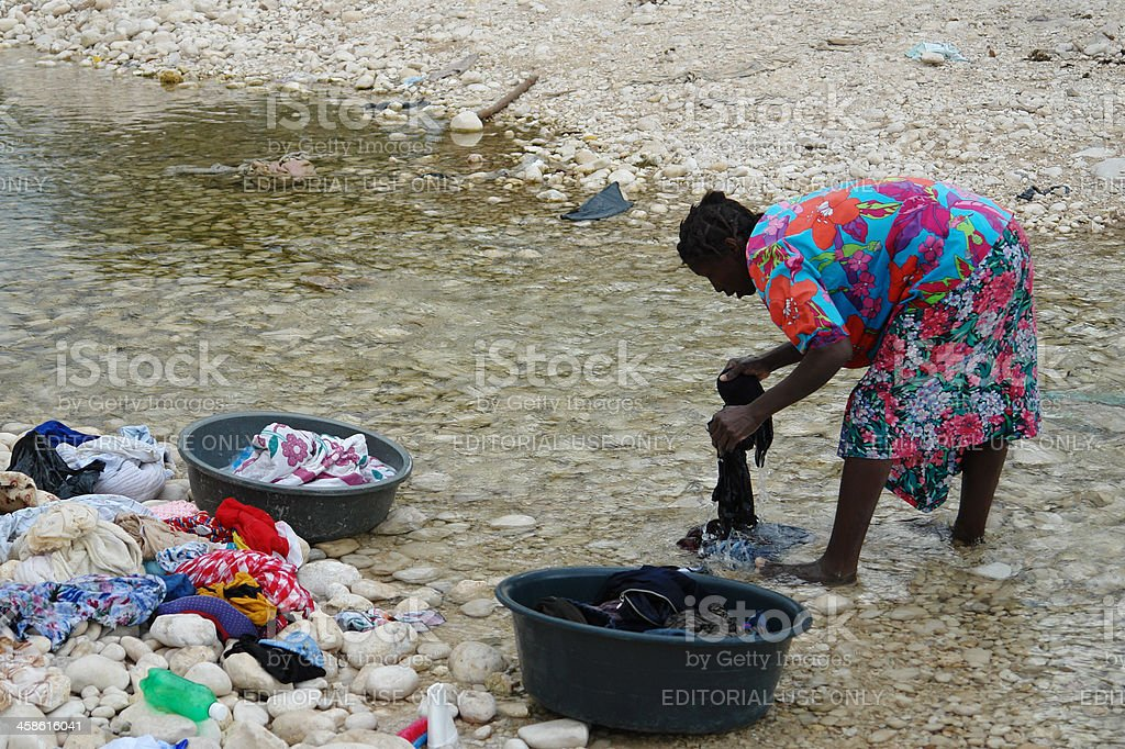 Haitian woman washing laundry in the river stock photo