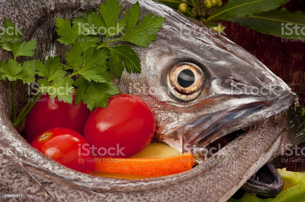 Hake fish being prepared for cooking with vegetables and herbs. stock photo