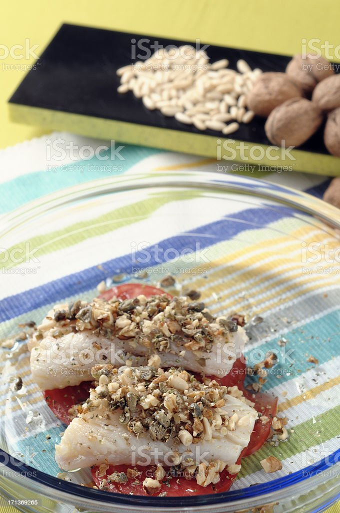 Hake with tomatoes, walnuts and pine nuts. royalty-free stock photo
