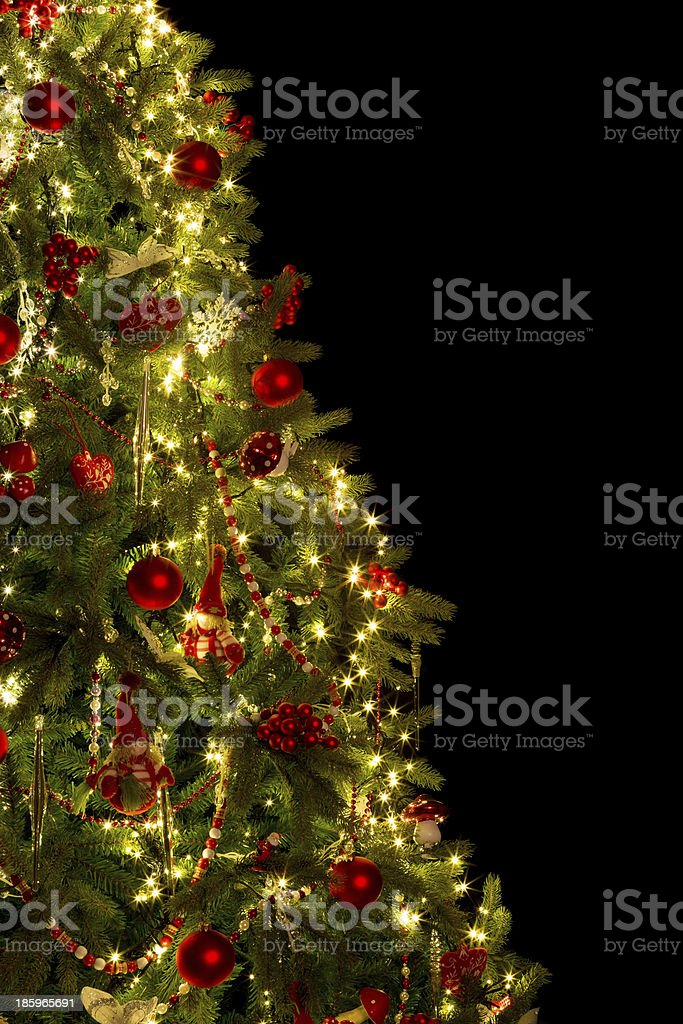 Half a Christmas tree adorned with red baubles and lights royalty-free stock photo
