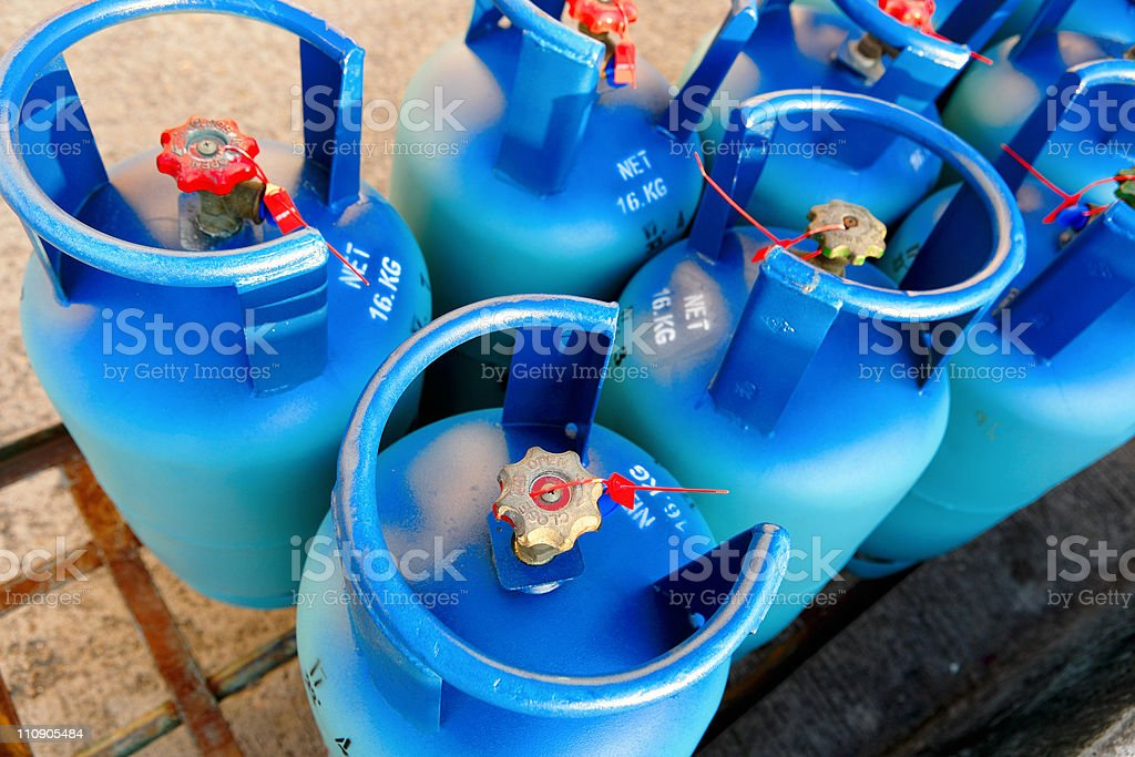 Half a dozen blue propane tanks stock photo