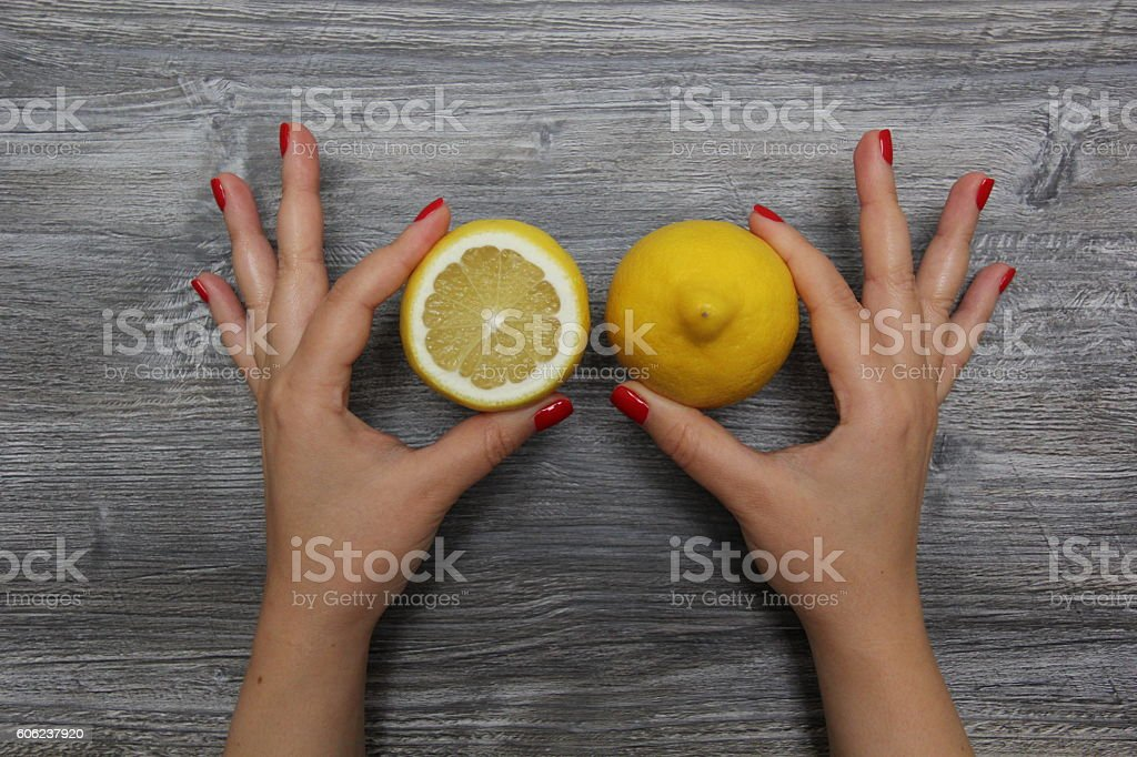 Half a lemon in the left hand and whole lemon in the right hand stock photo