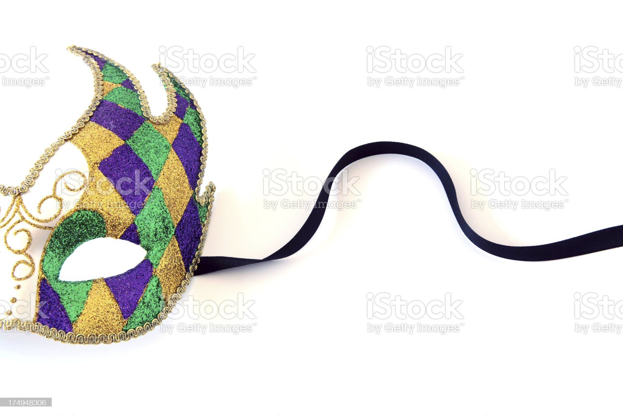 Half a purple gold and green harlequin mask with ribbon royalty-free stock photo