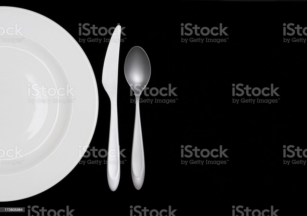 Half a white plate on black w silverware royalty-free stock photo