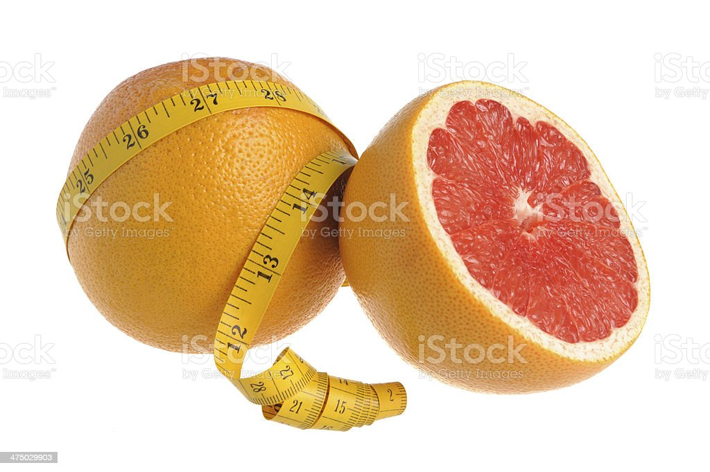 Half and whole grapefruit wrapped with measure tape on white stock photo