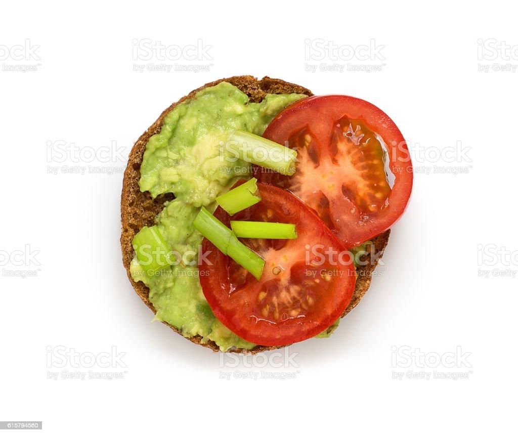 Half bun with avocado tomatoe and spring onions on white stock photo
