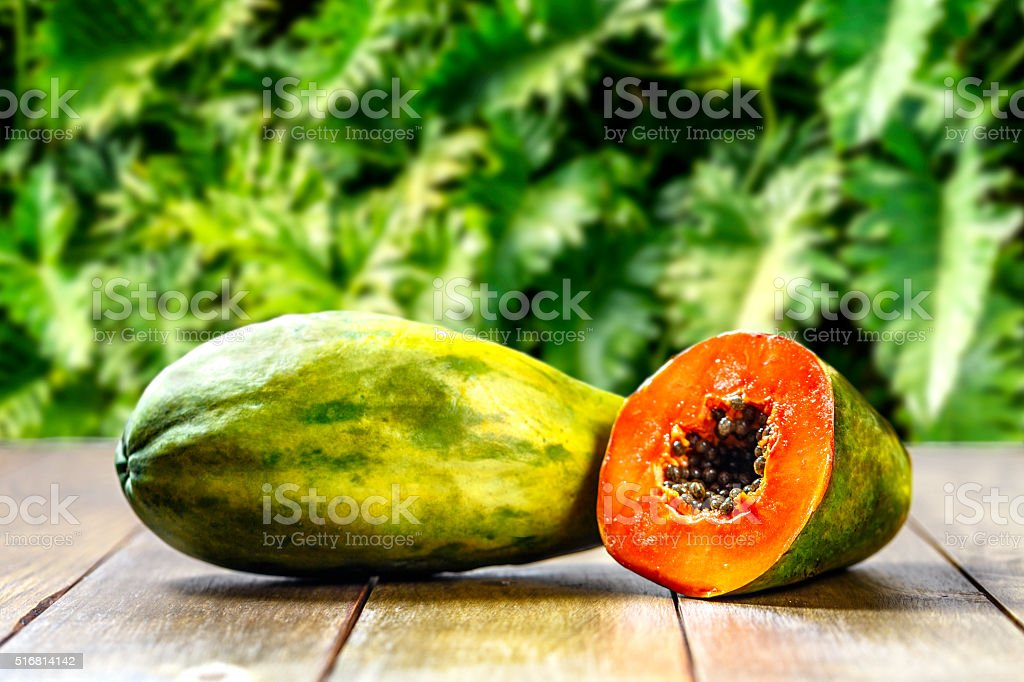 Half cut and whole papaya tropical fruits on wooden table stock photo