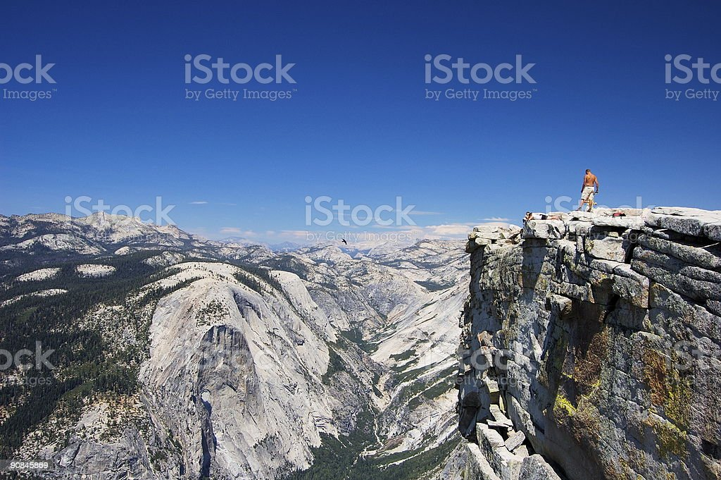 Half Dome rock with snow and person standing on the edge stock photo