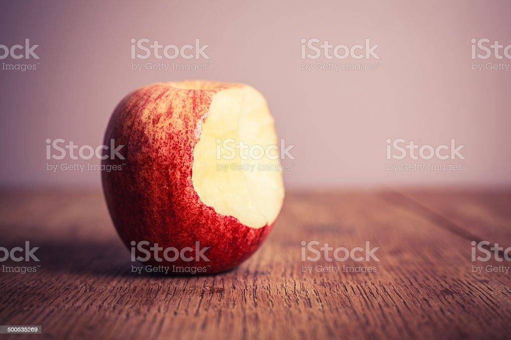 Half eaten apple on wooden table stock photo