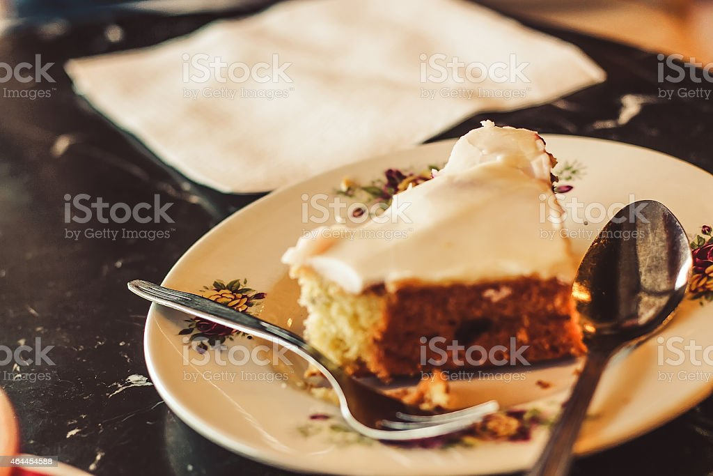 Half eaten cake with silver spoon stock photo