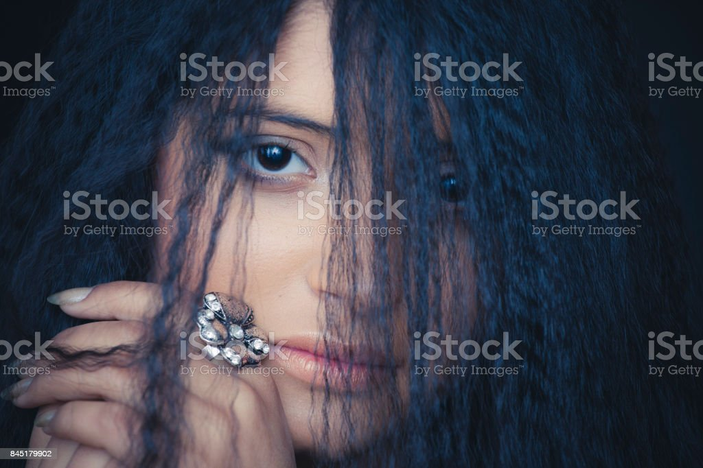 Half face covered with long hair of shy young woman. stock photo