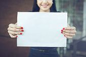 Half face of business woman holding an empty sign