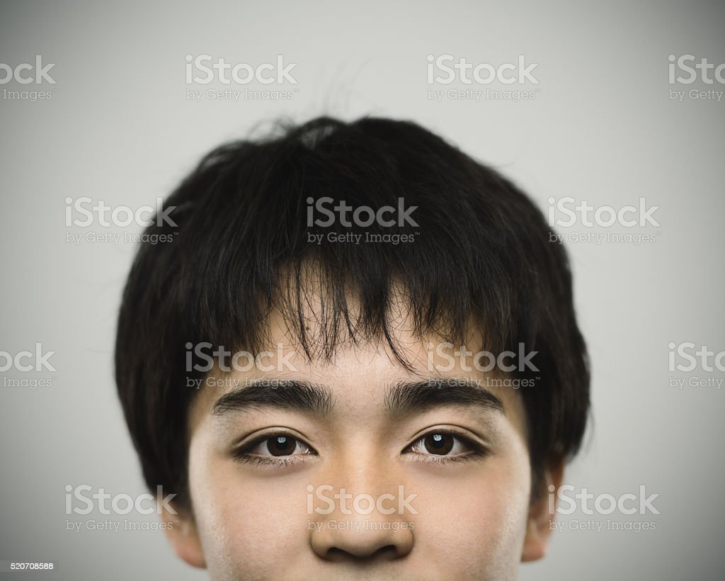 Half face portrait of a japanese teenager looking at camera stock photo