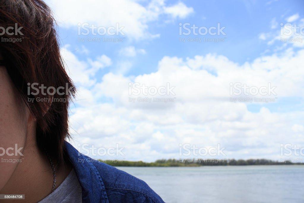 Половина лицо молодой мужчина носить джинсы и рубашку над голубое небо Стоковые фото Стоковая фотография
