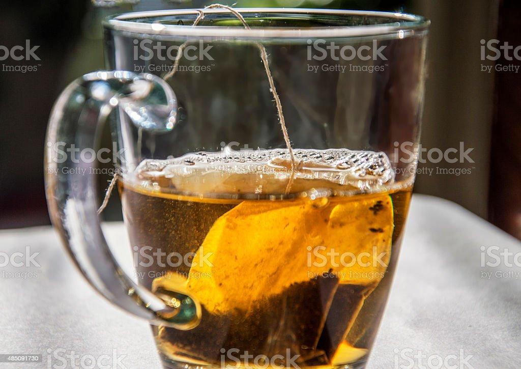 Half filled tea cup with tea bag stock photo