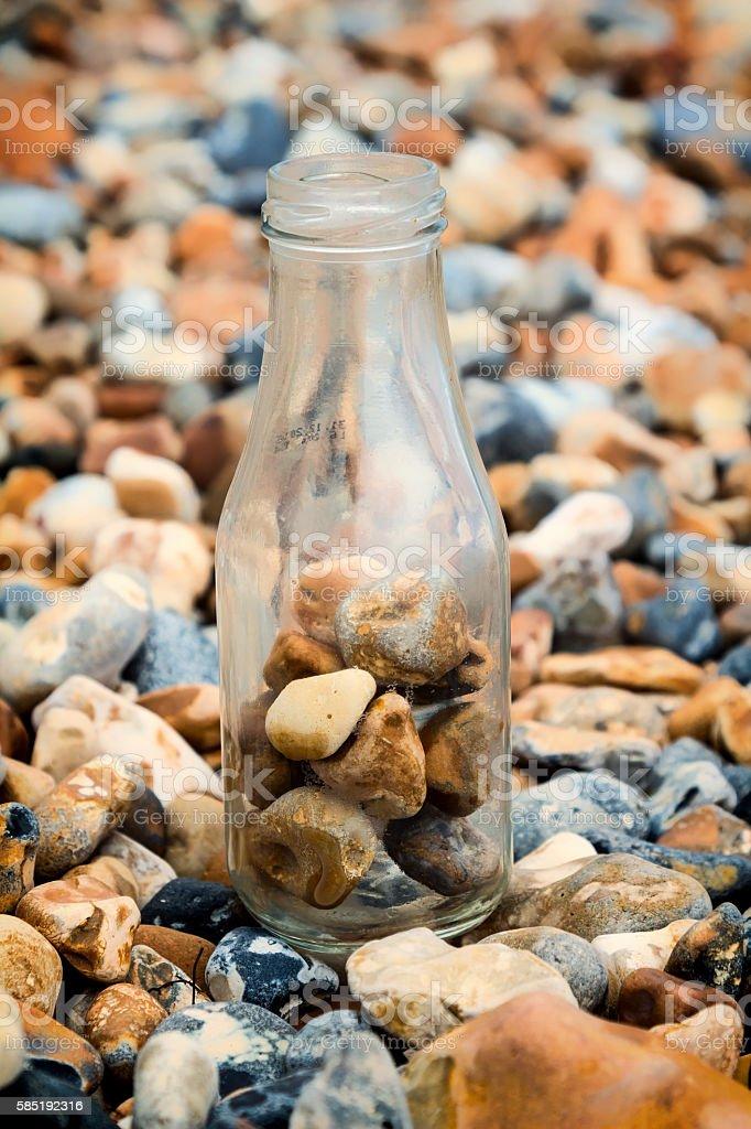 Half full bottle of stones stock photo