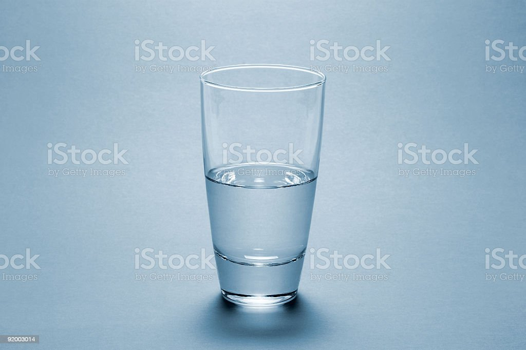 Half full water glass over blue background stock photo