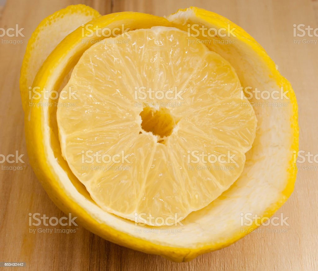 Half lemon cut and peeled with the skin stock photo