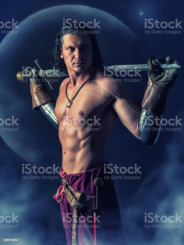half naked  warrior with a sword in the mystic background stock photo