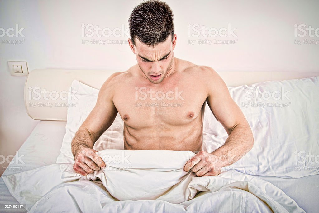 half nakedman in bed  looking down at his underwear stock photo