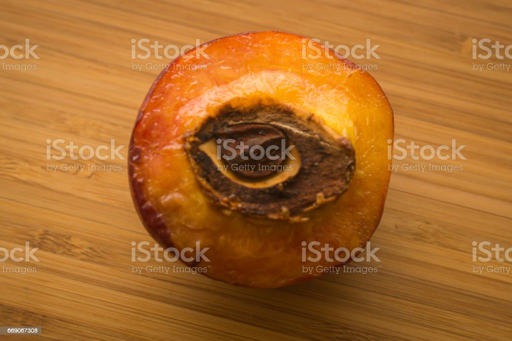 Half of a peach with stone in shape of an eye stock photo
